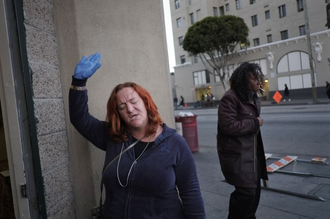 Trina Bohannan, a former homeless drug addict who now lives in a low-income apartment, sings along a song while ushering at a karaoke night at the Central City Community Church of the Nazarene in the Skid Row area of Los Angeles, Wednesday, May 8, 2013. (AP Photo/Jae C. Hong)