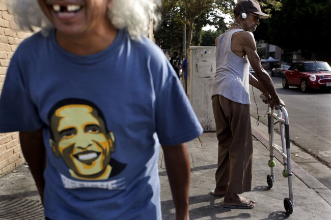 Cesar Solozano, 60, left, a former homeless man and a recovering drug and alcohol addict, laughs while waiting to cross the street in the Skid Row area of Los Angeles, Wednesday, July 3, 2013. (AP Photo/Jae C. Hong)
