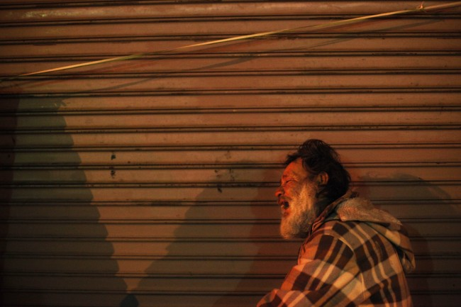 Jesse Raca, a 58-year-old homeless alcoholic, leans on the shutters of a closed store while trying to sleep in the Skid Row area of Los Angeles, Tuesday, March 19, 2013. (AP Photo/Jae C. Hong)