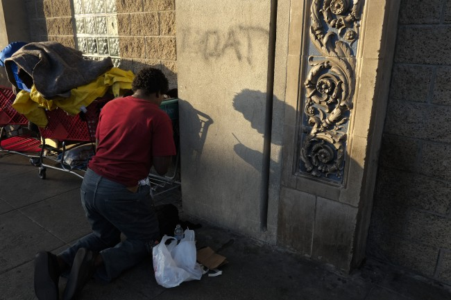A 25-year-old homeless drug addict prepares a needle to inject himself with heroin in the Skid Row area of Los Angeles, Thursday, April 25, 2013. It's not a rare scene on Skid Row to spot addicts using drugs in the open, even when police patrol the area. (AP Photo/Jae C. Hong)