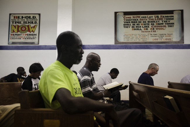 Homeless people attend a daily Bible study class at the Emmanuel Baptist Rescue Mission in the Skid Row area of Los Angeles on Thursday, July 18, 2013. The church doubles as a shelter for homeless men and the Bible study attendance is required in order to get a bed assignment. (AP Photo/Jae C. Hong)