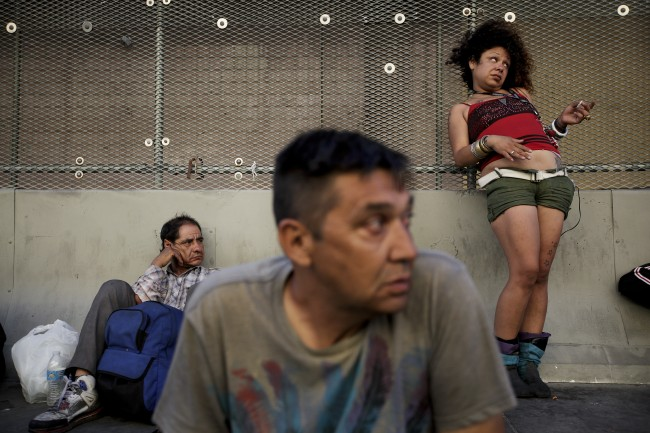 George Mendez, foreground, a 55-year-old recovering alcoholic, sits in front of a drunk woman in the Skid Row area of Los Angeles on Tuesday, July 23, 2013. The area, originally agricultural until the 1870s when railroads first entered Los Angeles, has maintained a transient nature through the years from the influxes of short-term workers, migrants fleeing economic hardship during the Great Depression, military personnel during World War II and the Vietnam conflict, and low-skilled workers with limited transportation options who need to remain close to the city's core, according to the Los Angeles Chamber of Commerce. (AP Photo/Jae C. Hong, File)