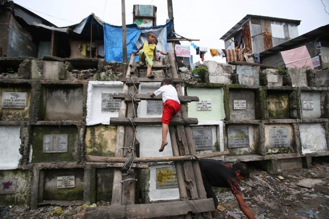 Filipino boys living on top of multi-layered tombs come down a ladder at a public cemetery in Navotas, north of Manila, Philippines on Thursday Oct. 31, 2013.