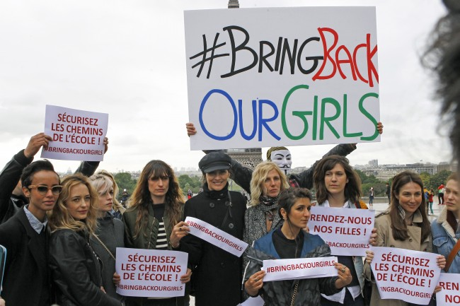 French actresses and models pose in front of the Eiffel Tower holding placards saying: Bring back our girls, during a rally at the Trocadero, to show support for the release of the kidnapped girls in Nigeria in Paris, Tuesday May 13, 2014. A French official says Nigerian President Goodluck Jonathan has agreed to attend a security summit on Saturday in Paris to focus on the Boko Haram terrorist network, which abducted more than 300 schoolgirls in Nigeria last month. Signs center and left read, save the Nigerian schoolgirls. (AP Photo/Remy de la Mauviniere)