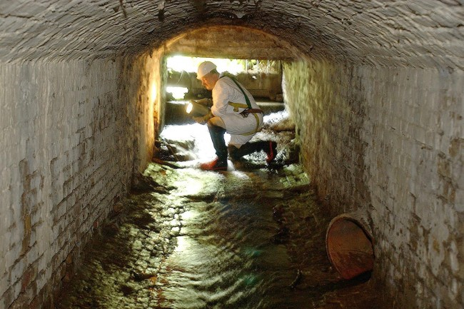 A sewage worker by the entrance to the sewer by the Serpentine in Hyde Park, west London.  2004.