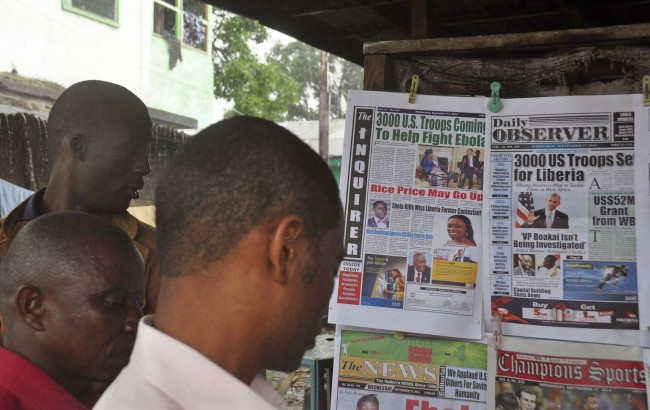 "People read newspaper headlines commenting on American President Barrack Obama's announcement on sending troops to fight the Ebola virus in Monrovia, Liberia, Wednesday, Sept. 17, 2014. Liberia's president called Wednesday on the world to do more to end a spiraling Ebola outbreak, saying ""Liberia cannot defeat Ebola alone."" President Barrack Obama announced Tuesday that he will order 3,000 military personnel to West Africa to help contain the dreaded disease, which has killed at least 2,400 people. The U.S. is also planning on delivering 17 treatment centers with 100 beds each to Liberia, which has been hardest hit by the outbreak. (AP Photo/Abbas Dulleh)"