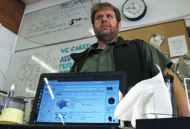 "John Schiff, owner of the Reuseum surplus store in Boise, Idaho, poses for a photo with a computer showing his company's ""Obtanium"" eBay store, Thursday, Oct. 2, 2014. Schiff says he has had a spike in sales of surgical masks on his site, which he attributes to public concern over the Ebola disease. (AP Photo/Lisa Baumann)"
