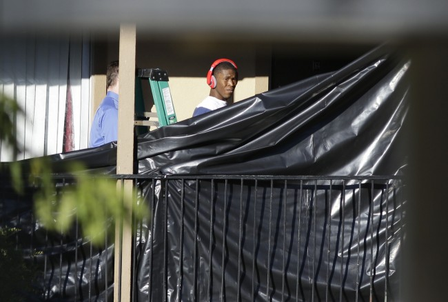 A young man prepares to leave an apartment in Dallas, Friday, Oct. 3, 2014, where Thomas Eric Duncan, the Ebola patient who traveled from Liberia to Dallas stayed last week. The family living there has been confined under armed guard while being monitored by health officials. (AP Photo/LM Otero)