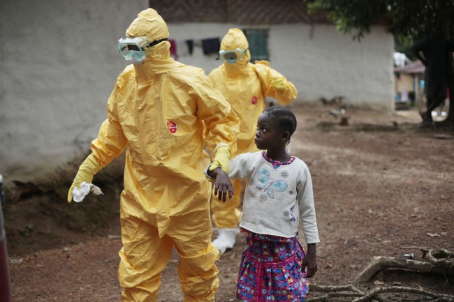In this Tuesday Sept. 30, 2014 file photo, Nowa Paye, 9, is taken to an ambulance after showing signs of Ebola infection in the village of Freeman Reserve, about 30 miles north of Monrovia, Liberia