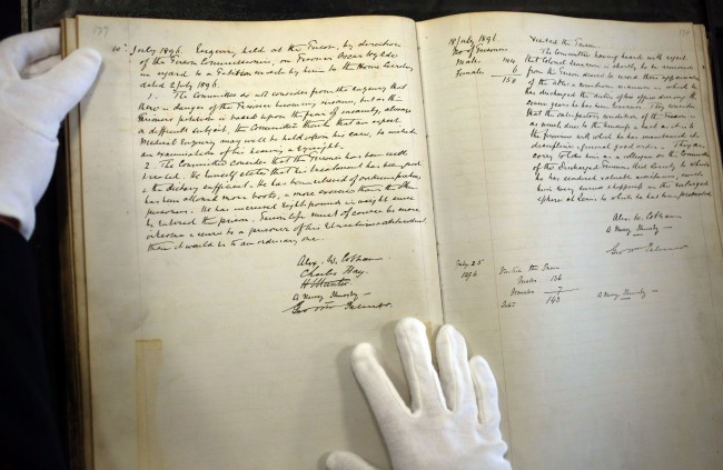 he hand of lead researcher Professor Peter Stoneley from the University of Reading, rests on a record of visits of the justices to Reading Prison opened to the page of July 10th 1896