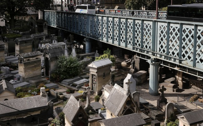 In this Oct. 13, 2014 photo, buses drive on a motorway over the Montmartre cemetery in Paris. Cemetery overcrowding is an issue that resonates around the world, particularly in its most cramped cities and among religions that forbid or discourage cremation. The reality of relying on finite land resources to cope with the endless stream of the dying has brought about creative solutions. (AP Photo/Jacques Brinon)