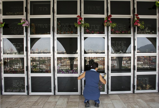 is Oct. 13, 2014 photo, an employee at the Necropole Ecumenica Memorial cleans the surface of crypts in Santos, Brazil. When completed, the five building memorial known as a vertical cemetery will hold 180,000 bodies. (AP Photo/Andre Penner)