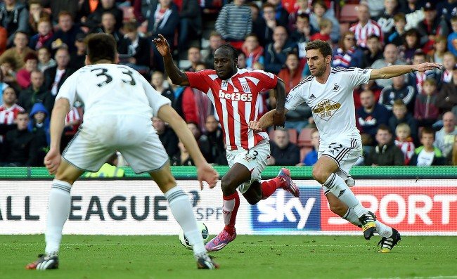 Swansea City's Angel Rangel fouls Stoke City's Victor Moses for a penalty, during the Barclays Premier League match at the Britannia Stadium, Stoke.