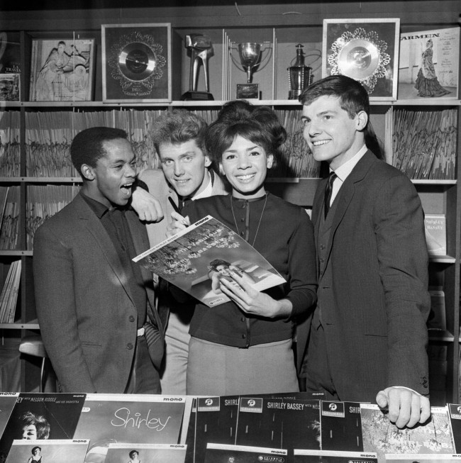 File photo dated 17/11/1962 of Alvin Stardust (second left), then known as Shane Fenton and born Bernard William Jewry, at Shirley Bassey's Record Shop on West End Lane, London with (from left) Danny Williams, Alvin Stardust, Shirley Bassey and Jess Conrad as the singer and actor Stardust has died this morning aged 72 after a short illness. Issue date: Thursday October 23, 2014. See PA story DEATH Stardust. Photo credit should read: PA/PA Wire Singing star Shirley Bassey autographs the sleeve of one of her own records at the opening of the Shirley Bassey Record Shop in West End Lane, London. Looking on are pop singers (l-r) Danny Williams, Shane Fenton and Jess Conrad.