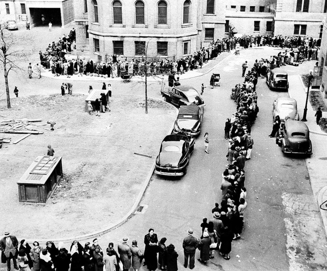 A long line of New Yorkers winds toward the entrance to Morrisania Hospital in the Bronx, New York April 14,1947, where doctors are innoculating against smallpox. They were attempting to half spread of the disease. Officials said city residents were being vaccinated at the rate of eight a minute. (AP Photo)