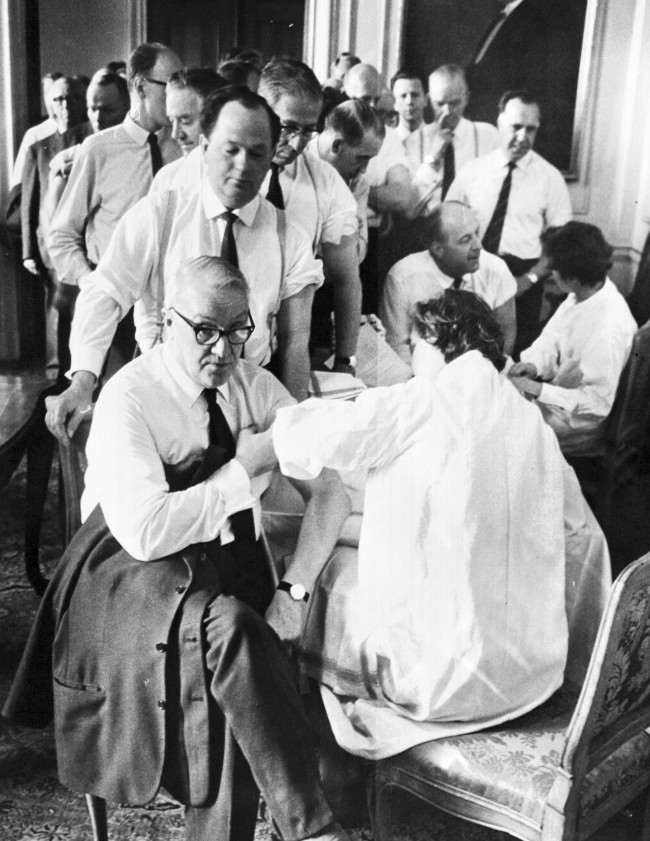 Hilding Hagberg, Swedish Communist Party leader, rolls up his sleeve as he receives a smallpox vaccination in Stockholm, Sweden. Other members of Sweden's Parliament line up behind to get their jabs. Date: 17/05/1963