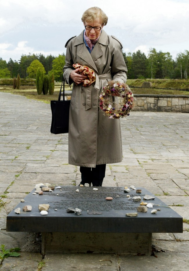 "Concentration camp survivor Anna Dobnik places a wreath of flowers on a memorial monument at the former concentration camp Bergen-Belsen in Germany where she was once a prisioner, Monday, May 24, 2004. She said ""I had the feeling that I should see these places again, and after so many years, relive these memories and bring flowers to the friends who died there."" (AP Photo/Fabian Bimmer) Date: 25/05/2004"