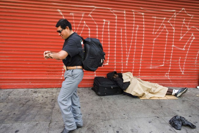 Homeless immigrant Luis Hernandez, originally from Puebla, Mexico, walks past another homeless person, as he goes to work, Sept. 14, 2005, in the Skid Row area of downtown Los Angeles. Among the estimated 14,000 people who live in Skid Row there exists a small shadow population of homeless immigrants who bed down each nigh in parks, abandoned buildings and find refuge in camouflaged encampments under freeway overpasses and bridges. (AP Photo/Damian Dovarganes)