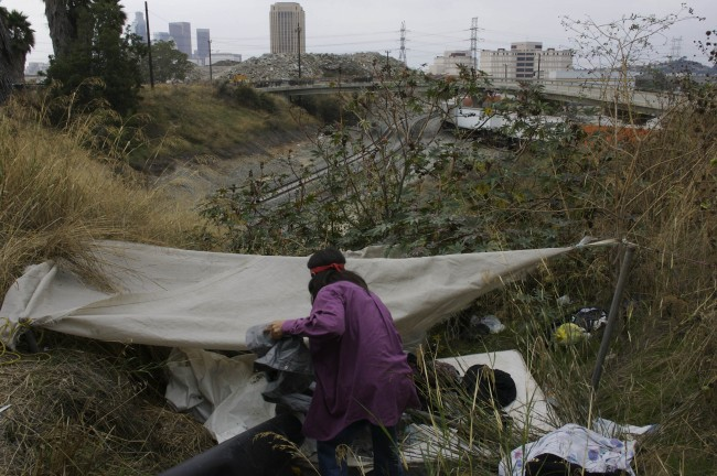 e Hernandez, a homeless immigrant, stores material in a makeshift shelter where he sleeps, in November 2005 near downtown Los Angeles. Among the estimated 14,000 people who live in Skid Row there exists a small shadow population of homeless immigrants who bed down each nigh in parks, abandoned buildings and find refuge in camouflaged encampments under freeway overpasses and bridges. (AP Photo/Damian Dovarganes)