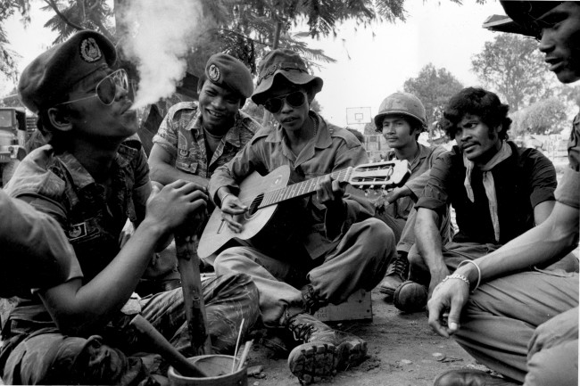 A Cambodian Army officer, left, exhales marijuana smoke after using a homemade pipe as a soldier plays guitar in Phnom Penh, Cambodia, 1973. (AP Photo/Chhor Yuthi) Ref #: PA.3826161  Date: 00/00/1973