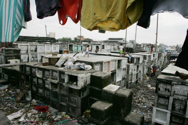 "Children living inside a public cemetery compound play on top of ""apartment type"" cemeteries at Navotas north of Manila, Philippines, Tuesday, Oct. 31, 2006."