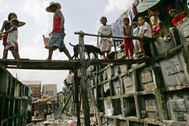 A man crosses a foot bridge to spruce up the tomb of the departed loved one as children living on top of dilapidated tombs while away their time at a public cemetery at Navotas north of Manila Tuesday Oct. 31, 2006.