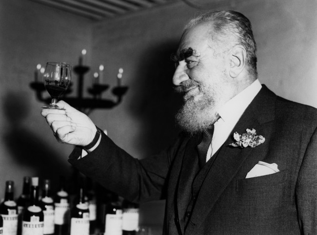 Nubar Gulbenkian, the well known oil magnate, examines a Vintage Claret during the French wine tasting reception held in the cellars of Lebegue, the well known London wine merchants Ref #: PA.4410347  Date: 09/10/1964