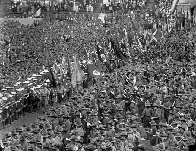 Scouts parade with their Colours passing through the vast crowd at the Jamboree. Date: 03/08/1924