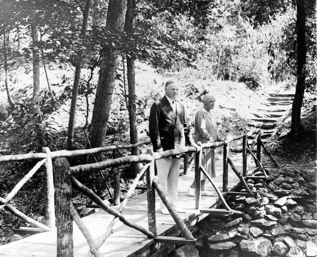 U.S. President Herbert Hoover and his wife, Lou Henry Hoover, pause on a bridge as they take a stroll at Rapidan Camp, their weekend retreat in Syria, Va., on Aug. 2, 1930. (AP Photo)
