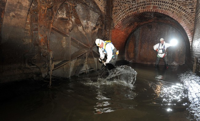 Rob Smith,left, a 'flusher' with Thames Water clears away a mixture of water and fat, that builds up in the sewers under London due to cooking fat being poured down drains