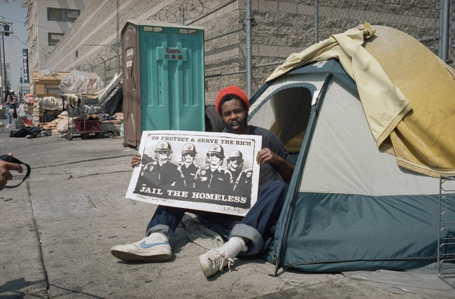 Thirty year-old Steve Davis, homeless for three months in downtown Los Angeles, Thursday, June 4, 1987, displays a banner that emphasizes his feelings about the planned sweep of the Skid Row area by the police of those illegally encamped along sidewalks. (AP Photo/Nick Ut)