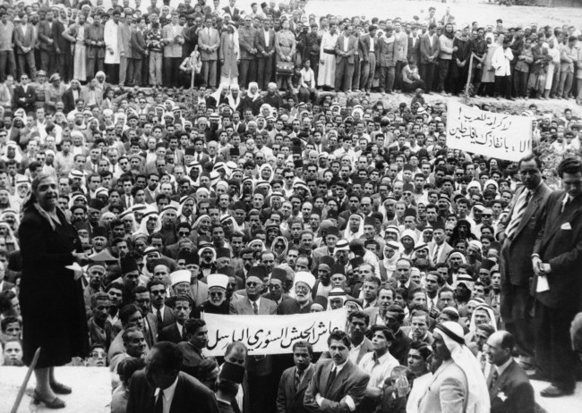 Some 10,000 of the 48,000 Palestine Arab Refugees who have settled in and around Damascus, Syria, staged a demonstration in Damascus, last week in April 1929 to express their gratitude to the Syrian Army for the recent Syria-Israel border clashes. They asked to be accepted as volunteers for the Syrian fighting forces so that they night fight back at Israel, upon which country they blame their present unhappy condition as refugees. Photo shows: An elderly lady addresses a great crowd of Palestine Arabs in the court-yard of the Army General Headquarters in Damascus. Her speech was among others heard there by Syrian Officers. (AP Photo) Ref #: PA.7380130  Date: 01/04/1929