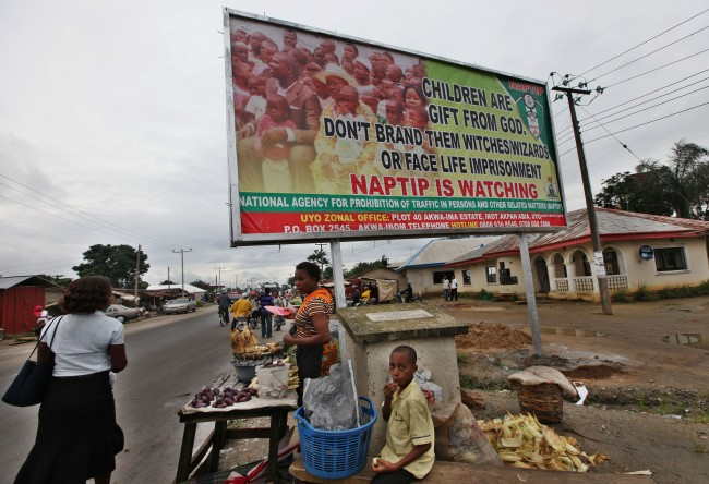 "This Aug. 17, 2009 photo shows a vendor selling maize under a sign reading, ""Children are gift from God. Don't brand them witches/wizards or face life imprisonment,"" in Akwa Ibom, Nigeria. The idea of witchcraft is hardly new, but it has taken on new life recently partly because of a rapid growth in evangelical Christianity. Campaigners against the practice say around 15,000 children have been accused in two of Nigeria's 36 states over the past decade and around 1,000 have been murdered. (AP Photo/Sunday Alamba)"