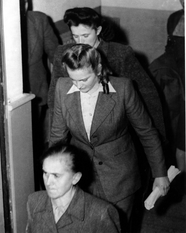 Irma Grese, center with her head bowed, leaves the courtroom in Lueneburg, Germany on Nov. 16, 1945. Grese, who was an SS supervisor at the Bergen-Belsen concentration camp, and 29 others were found guilty of war crimes. She was executed the following day. (AP Photo)