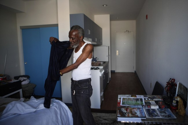 Edward Merida, a 71-year-old Project 50 participant, gets dressed for dinner in his room at the Charles Cobb Apartments, a home for Project 50 participants, in Los Angeles, Thursday, July 15, 2010. The Project 50 is a pilot program to get the 50 people most likely to die if they remained homeless into housing, medical care and social services. (AP Photo/Jae C. Hong)