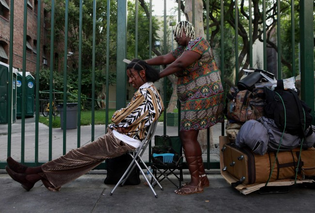 Tanika Smith, right, braids Donald Reese's hair in the Skid Row area of downtown Los Angeles, Wednesday, Sept. 29, 2010. (AP Photo/Jae C. Hong)