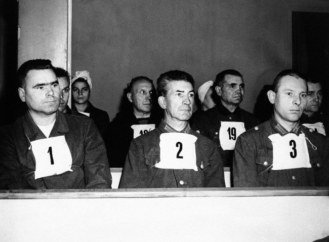 "The first of the war criminal trials to be held in Germany, when Josef Karmer, ""The Beast of Belsen"" took his stand in the specially prepared courtroom at Luneburg, together with 29 men and 19 women who will also be charged with the ill-treatment of Allied war prisoners. Josef Kramer, former head of Belsen Horror Camp wearing a placard marked No. 1 on his left is Fritz Klein, No. 2, and right, Peter Weingartner, No. 3, seen in the courtroom at Luneburg, Germany, on Sept. 17, 1945. (AP Photo)"