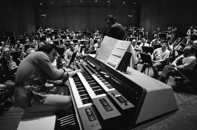 "Lalo Schifrin, Argentine-born composer, rehearses his electronic music-making monster called the Electronic EX-42 with the Los Angeles Philharmonic under Zubin Mehta's direction for the world premiere of his ""Pulsations"", Jan. 27, 1971. The contrivance is part of an electronic musical explosion with widespread implications for producers and musicians. (AP Photo/George Brich)"