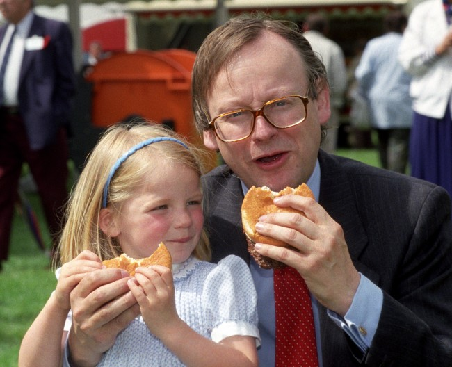 Agriculture minister John Gummer with his 4 year old daughter Cordelia, tuck into a beefburger on a visit to the East Coast Boat Show in Ipswich. The possilbe danger of the BSE disease in British beef was scuppered by the minister. * in an attempt to calm public fears when the beef scare first broke in 1990. Mr Gummer, now Environment Secretary snapped angrily at James Naughtie, presenter of Radio 4's Today programme, when he asked if Mr Gummer now regretted posing for the picture. *25/10/2000 Mr Gummer and other senior members of the Thatcher and Major administrations are bracing themselves for harsh criticism of their handling of the BSE crisis, as the Government publishes the long-awaited results of the inquiry into Britain's biggest public health disaster. Lord Phillips' report, to be published Thursday October 26 2000 is expected to condemn the former Tory government's slow reaction to the crisis and ministers' refusal to accept that humans might be made ill by eating beef from infected cows. 26/10/00: Mr Gummer and other senior members of the Thatcher and Major administrations are bracing themselves for harsh criticism of their handling of the BSE crisis, as the Government publishes the long-awaited results of the inquiry into Britain's biggest public health disaster. Lord Phillips' report, published Thursday October 26 2000, is expected to condemn the former Tory government's slow reaction to the crisis and ministers' refusal to accept that humans might be made ill by eating beef from infected cows. Ref #: PA.1248798  Date: 16/05/1990