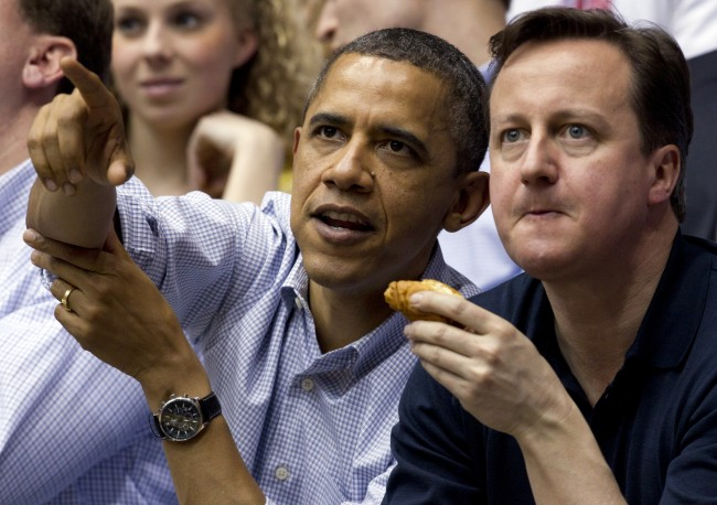 President Barack Obama and Britain Prime Minister David Cameron eat hot dogs as they attend the Mississippi Valley State versus Western Kentucky in a first round NCAA tournament basketball game, Tuesday, March 13, 2012, at University of Dayton Arena, in Dayton, Ohio. (AP Photo/Carolyn Kaster)