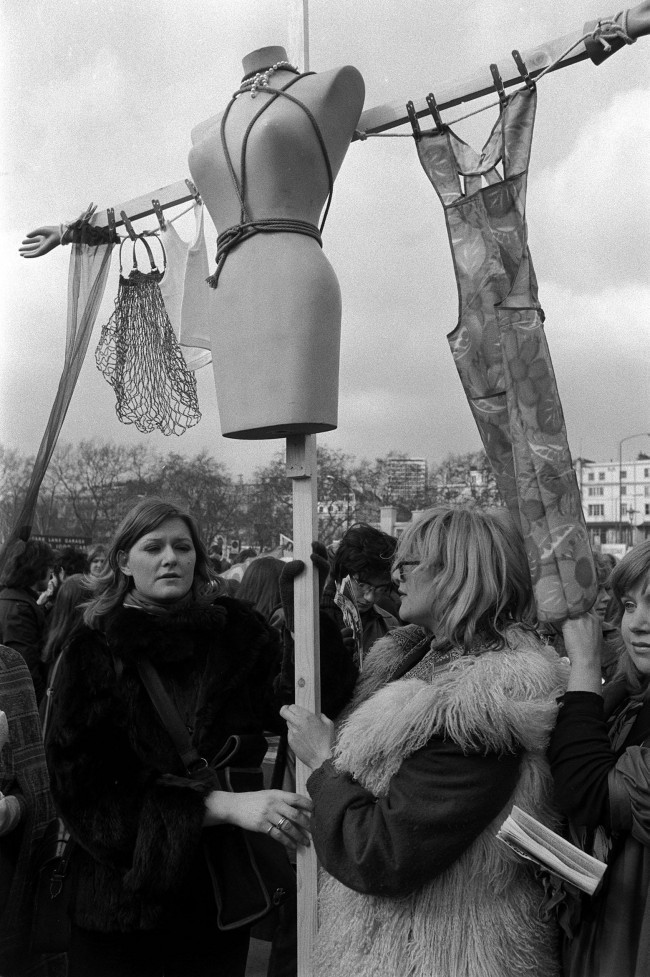 "The dressmaker's dummy, the kitchen apron, the shopping bag and the clothes line all figured in this ""banner"" carried by Stephanie Gilbert, (L) and Judy Gilbert-Scott as militant women rallied at speaker's corner, Hyde Park. Date: 06/03/1971"