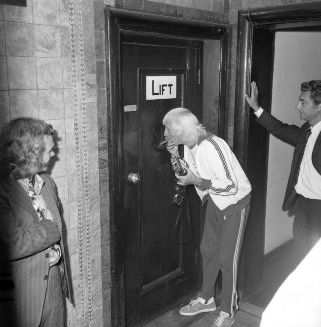 TV and radio star Jimmy Savile entertains schoolchildren trapped in a broken-down lift in London. The youngsters were being presented by Mr Savile with a £7,500 cheque for the National Society for the Prevention of Cruelty to Children. Archive-163375-1 Ref #: PA.14859346  Date: 07/09/1973