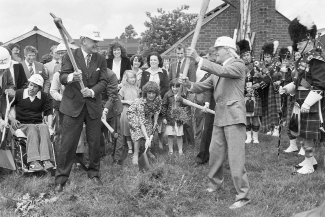 Jimmy Savile (right) and Dr Gerard Vaughan, Minister for Health, at Stoke Mandeville Hospital in Buckinghamshire, where a National Spinal Injuries Centre is being built. Also attending the ceremony, in which Jimmy announced plans for a new appeal, are patients, staff, and a pipe band from the Royal Artillery Force. Archive-PA192863-1 Ref #: PA.14897527  Date: 16/06/1980