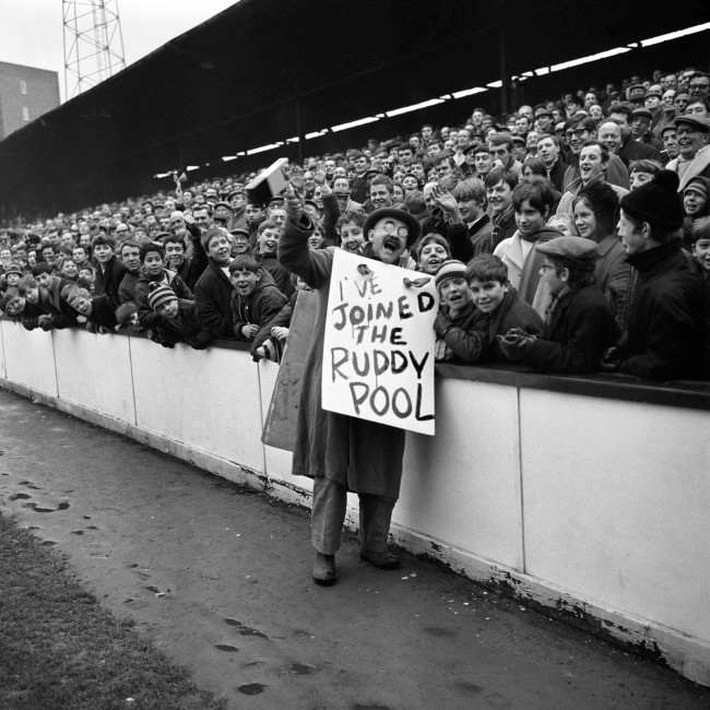 West Ham United fan Warren Mitchell, alias Alf Garnett of BBC series 'Til Death Us Do Part', tries to drum up support for the Hammers' Pool by roaming around Upton Park with a rattle and sandwich board Ref #: PA.2343522  Date: 03/02/1968