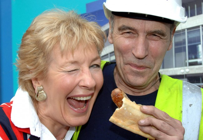 Christine Hamilton tries a sausage butty from London's Quality Chop House,with the help of construction worker Peter Bramhall, from Barnsley, in London on Monday October 24, 2005, to mark British Sausage Week of which Mrs Hamilton is the 'face'. The country's sausage consumption has risen 17\% to an estimated 189,000 tonnes between 2000 and 2005 in a market which is now worth £530 million per annum. PRESS ASSOCIATION Photo. Photo credit should read: Fiona Hanson/PA.