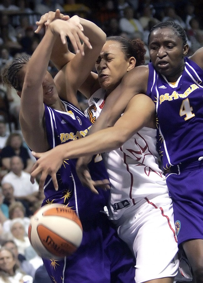 The Los Angeles Sparks Christi Thomas, left, and Mwadi Mabika, right, team up to sandwich the Connecticut Sun's Erika de Souza, of Brazil, between them as the three battled for a loose ball in the second half of the Sun-Sparks WNBA basketball game in Uncasville, Conn., Saturday, May 26, 2007. The Sparks defeated the Sun, 88-68. (AP Photo/Bob Child) Ref #: PA.4694155  Date: 26/05/2007
