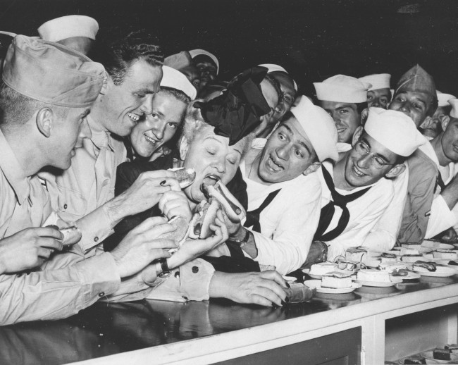 Sailors joke with radio personality Sophie Tucker and feed her multiple hot dogs at the United Service Organizations (USO) center in Chicago, Ill., July 2, 1944. From left are, Marine Pvt. Art McCarroll, of Pittsburgh, Pa.; Corp. Verne Hink, of Oklahoma City, Okla.; Seaman Fred Bishara, Binghamton, N.Y.; and Seaman Alan Frank, Salt Lake City, Utah. (AP Photo)
