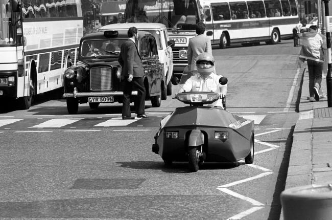 Mike Barnes, of Derby rides around Parliament Square in his invention the 'Nippi' motorbike, designed for the disabled. The bike is designed to take both rider and wheelchair. Ref #: PA.5509338  Date: 17/07/1984