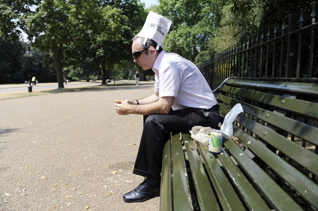 An office worker during his lunch break in London's Hyde Park, tries to keep the sun from his head by using a sandwich bar bag as a sun hat during the hot weather. Picture date: Thursday July 2, 2009. See PA story WEATHER Hot. Photo credit should read: Nick Ansell/PA Ref #: PA.7518903  Date: 02/07/2009