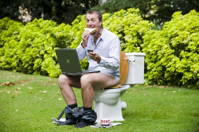 EMBARGOED TO 0001HRS MONDAY AUGUST 24 Television personality and former cricketer Phil Tufnell demonstrates some of the activities that British people get up to whilst on the toilet in London's Paddington Street Gardens for the launch of Gut Week, a campaign that aims to raise awareness of gut disorders and the importance of good digestive health, which runs from Monday 24th until 30th August.  Issue date: Sunday August 23, 2009. According to a survey of over 2,000 people conducted by Yakult, British people are spending their toilet time texting, surfing the internet and even eating and drinking whilst unaware of the health risks of sitting on the toilet for too long. PRESS ASSOCIATION Photo. Photo credit should read: Matt Crossick/PA Wire Ref #: PA.7733931